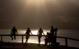 Group in silhouette at Byron Bay lighthouse at sunset