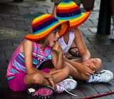 Sisters with colourful hats watching busker