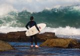 Surfer contemplating heavy surf