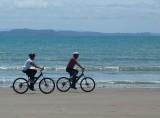 Biking along Manly Beach Whangaparaoa.