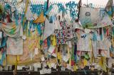 Fence at the end of the bridge festooned with t-shirts, ribbons, etc. left by visitors.