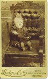 If you look closely you will see what looks like a box under the child's cloths. I believe that he has passed as this photos came with many other postmortem photos. His hand may have fallen during the photo process. The photo is by one of Montreal premier photographers for this type of photo( postmortem). I have had many comment on this image and I am now perplexed is he alive or has he left his body?
