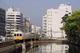 Kotoden train passing the castle moat