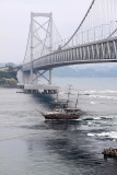 Old-style boat passing under the bridge