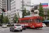 Traffic passing a bright red roman-densha