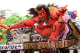 Demon figure atop the back of a float