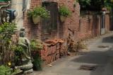 Buddhist statue along a brick-walled lane