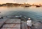Man sitting next to Sultan Qaboos Port in Mutrah