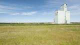 A grain elevator on a blue sky prairie landscape.