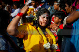 A devotee with cheeks pierced carry a milk pot in the procession