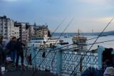 Turkish men fishing on Galata Bridge with Karakoy Pier and early morning sea bus on Boshphorus Istanbul