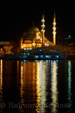 The New Mosque in early morning before sunrise with lights reflected in the Golden Horn Istanbul