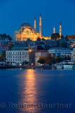 Lights of Suleymaniye Mosque Istanbul reflected at dawn on Golden Horn water