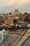 Fishing rods for sale on Galata Bridge over Golden Horn with Suleymaniye Mosque Istanbul