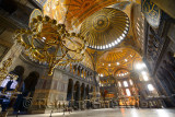 Morning light in an empty Hagia Sophia with chandeliers and golden dome