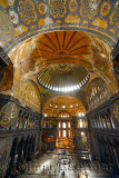 Golden domes frescoe and crooked Qiblah wall inside the Hagia Sophia with wood pendants