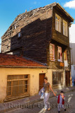 Woman and child walking by old run down Historic Ottoman wooden house in Istanbul Turkey
