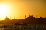 Blue Mosque and Hagia Sophia minarets silhouettes at sundown over the Bosphorus with backlit boat Istanbul