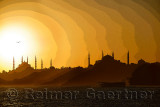 Posterized silhouette of Blue Mosque and Hagia Sophia at sundown over the Bosphorus with boat Istanbul