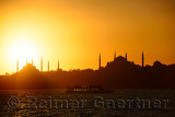 Sun setting over Blue Mosque with Hagia Sophia in silhouette on the Bosphorus with boat Istanbul