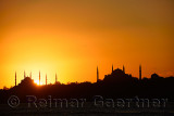 Sun setting behind Blue Mosque with Hagia Sophia in silhouette on the Bosphorus Istanbul