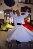 Male Sufi Whirling Dervish in white at a Sema Ceremony with musicians and women at Istanbul train station