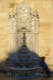 Young boy at stone fountain with shadow of a dome at Eyup Sultan Mosque Istanbul