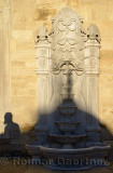 Shadow of a bearded man and dome on carved marble fountain at Eyup Sultan Mosque Istanbul