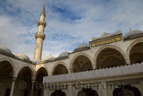 Minaret in sun from inner courtyard with ablution fountain at Suleymaniye Mosque Istanbul