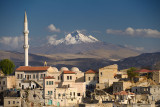 Houses and Mosque in Ortasihar with view of Mount Erciyes dormant volcano Cappadocia Turkey