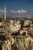 Houses and Mosque in Ortasihar with view of Mount Erciyes and tuff hoodoos Cappadocia Turkey