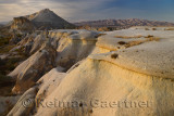 Eroded volcanic tuff lit by evening sun at Pasabag Monks Valley with Avanos beside distant hills Cappadocia Turkey