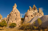 Ancient cave houses carved out of volcanic tuff at Uchisar with evening sun Cappadocia Turkey
