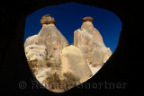 View of two Fairy Chimneys with sphynx on the left through a window of a cave Urgup Turkey