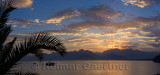 Panorama of Antalya Harbour Turkey with sunset sunbeams over mountains palm tree and tall ship