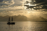 Mediterranean Sea at Antalya harbour Turkey with sunset sunbeams over mountains and tall ship