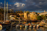 Tall ships and boats in at Antalya harbour Turkey with Roman wall fortificaiton at sundown