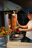 Man slicing roasted lamb from a Gyro heated by a vertical wood oven in Antalya Turkey