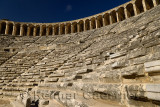 View of semicircular stone seats at ancient Aspendos theatre from the stage with upper gallery arches in Turkey
