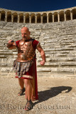 Roman Gladiator with sword in sun on stage at the ancient Aspendos theatre Turkey