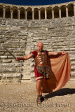 Roman Gladiator with sword spreading cape in sun on stage at the ancient Aspendos theatre Turkey