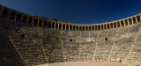 Panorama of semicircular stone seats at ancient Aspendos theatre with upper gallery arches and stage in Turkey