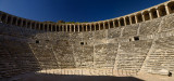 Panorama of semicircular stone seats at Aspendos Amphitheatre with upper gallery arches and stage Turkey