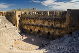 View of Aspendos theatre stage facade and distant hills from upper gallery with groups of tourists in Turkey