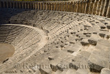 Semicircle of stone seats at Aspendos Amphitheatre with upper gallery arches and stage Turkey