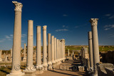 Colonade of ancient pillars at Agora of Perge ruins Turkey with hilltop Acropolis