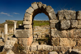 View through an arch of the main street colonade with pool and Acropolis at Perge Turkey archaeological site