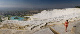 Panorama of woman in bikini on white travertine terraces at Pamukkale hot springs Turkey overlooking village and valley