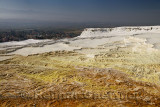 Red yellow white travertine terraces at Pamukkale hot springs overlooking the village and Curuksu plainTurkey