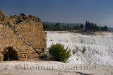 Ancient stone wall of Hierapolis ruins and tourists at thermal waters of Pamukkale Turkey